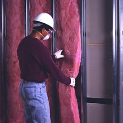man wearing hardhat, gloves and filter mask installing fiberglass insulation between wall studs