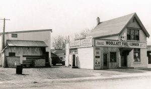 """Woollatt's original building from the late 1950s. Photo depicts a small two storey building with the sign """"Woollatt Fuel & Lumber"""" as well as a second building on the left behind the main building."""