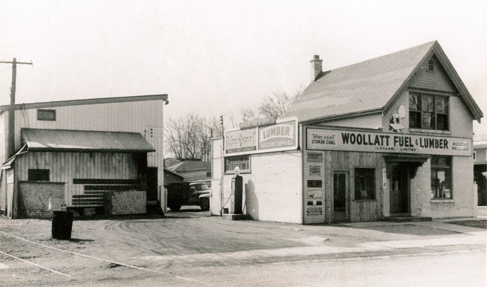 "Woollatt's original building from the late 1950s. Photo depicts a small two storey building with the sign ""Woollatt Fuel & Lumber"" as well as a second building on the left behind the main building."